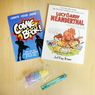 a Create Your Own Comic Book book, Lucy and Andy Neanderthal, bubbles, and chalk from a Sioux City Public Library Summer Quest Kit