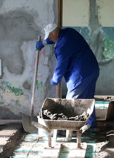 A barrow of cement is brought for spreading