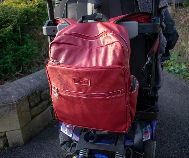 Close up of red Mia Tui backpack on the back of powerchair