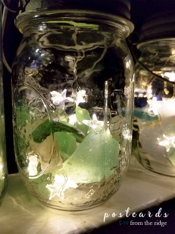 mason jar lanterns with sea glass and solar powered lids with fairy lights