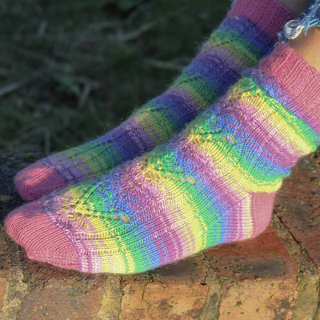 A pair of socks knitted to the Adeline pattern in WYS Wildflower and Honeysuckle
