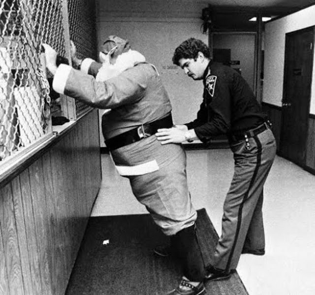 Volunteer Santa Claus arrested in New Jersey. Officer frisks santa at the station. c.1980s A Pleasant Christmas Story and other stories of Christmas Creepers. marchmatron.com