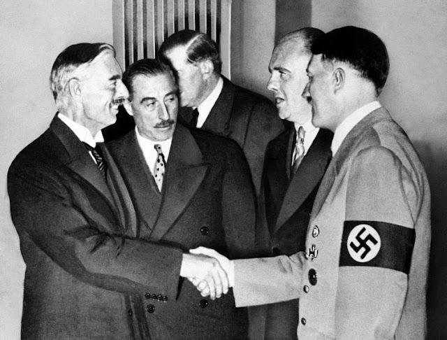 Hitler shakes Neville Chamberlain's hand in Munich worldwartwo.filminspector.com