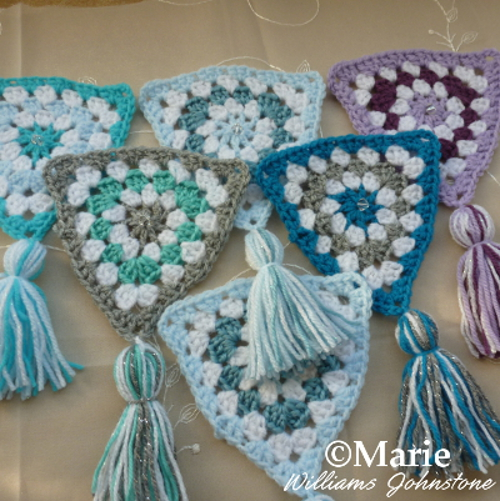 Crochet granny triangles with tassels made in winter colors of blues, whites and cool lilacs see the full tutorial