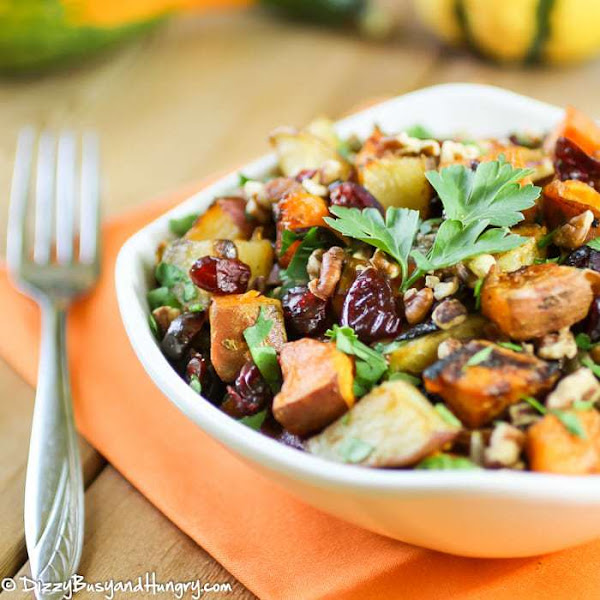 Side view of a roasted potato medley with cranberries and pecans in a white bowl.