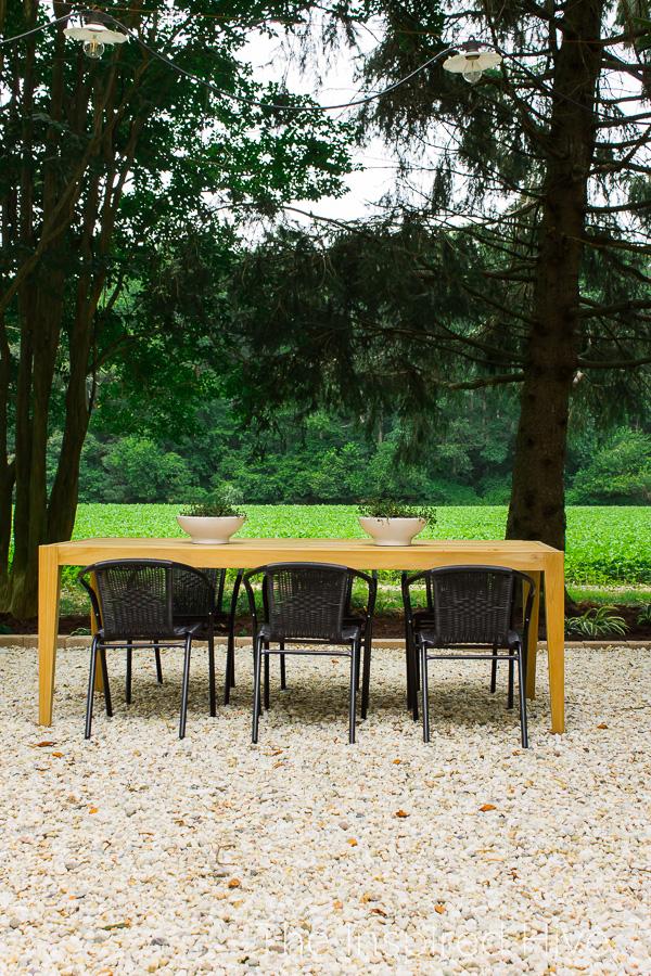 Teak dining table on gravel patio