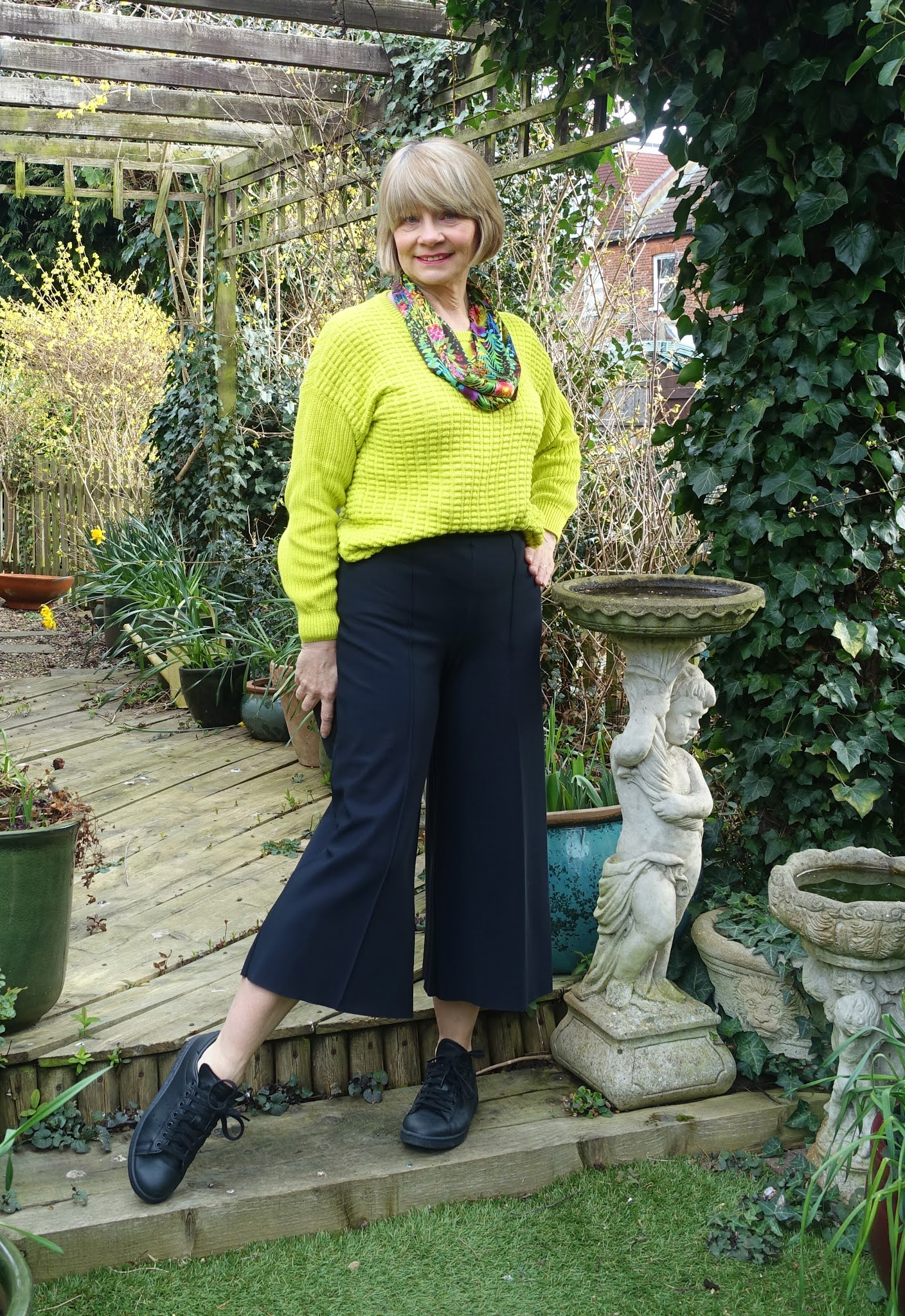 A colourful Liberty print scarf adds spring color to a lime green jumper