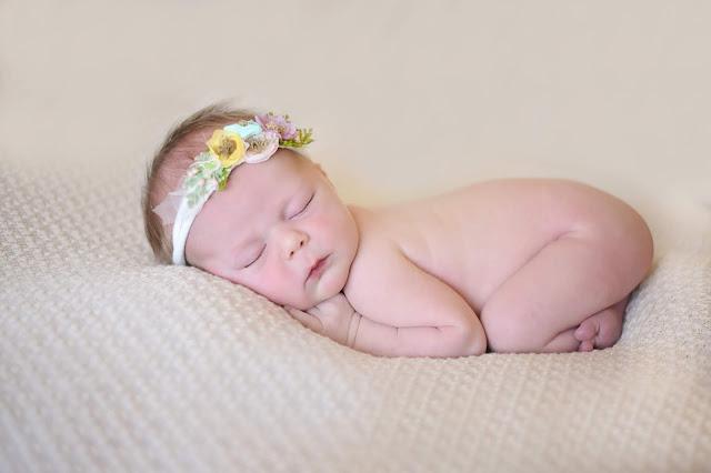 newborn girl on beige blanket
