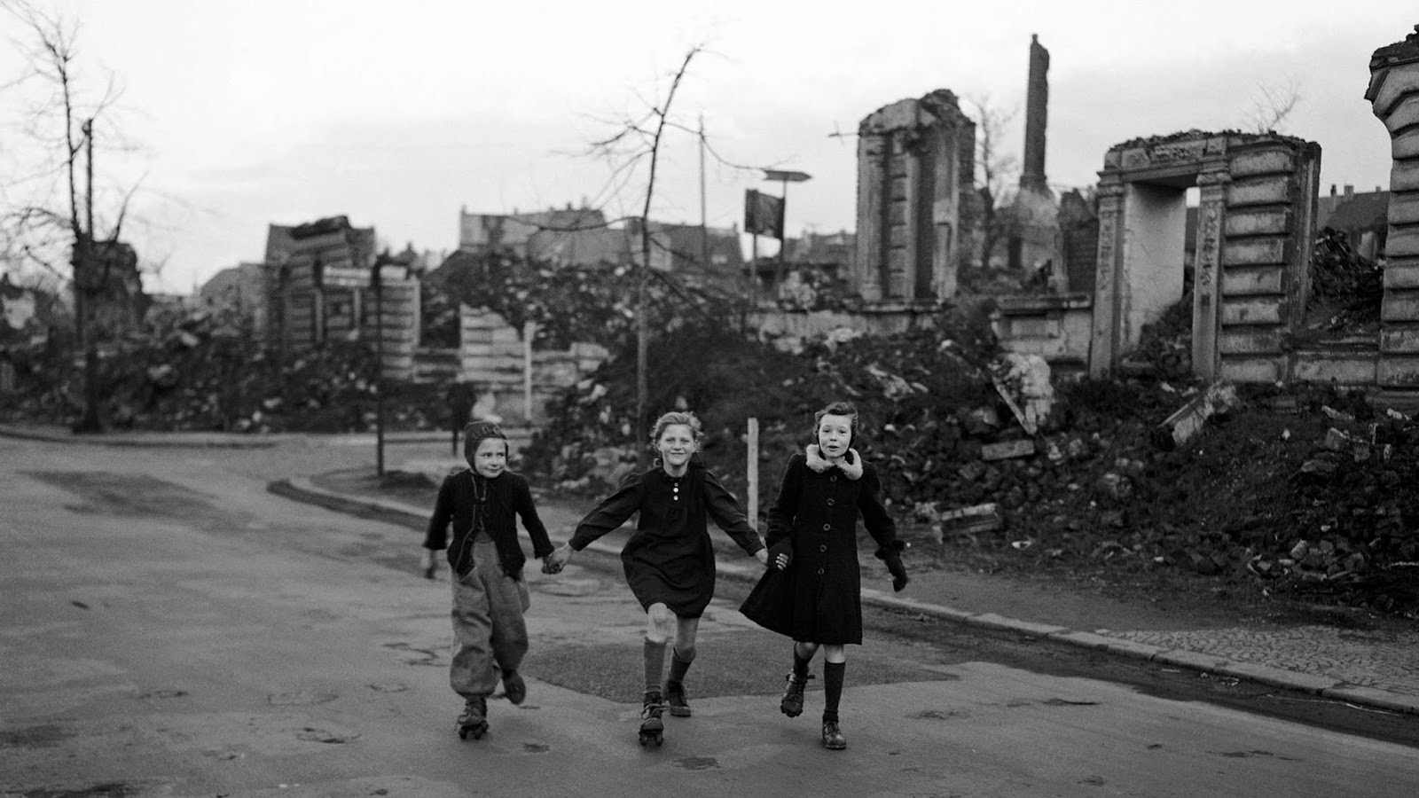 Three girls skate home from school, past blocks of houses destroyed by Allied air raids, Essen, Germany, February 14, 1949.