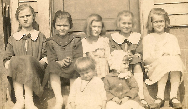 Close up of 7 girls sitting on a stoop. Possibly 1920's? Ages from toddler to teen.