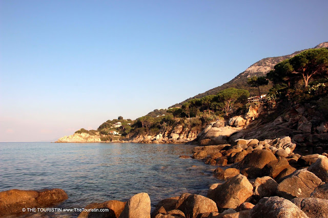 Boulders on a sandy beach on the foot of a mountain range in the soft evening light of the blue hour..