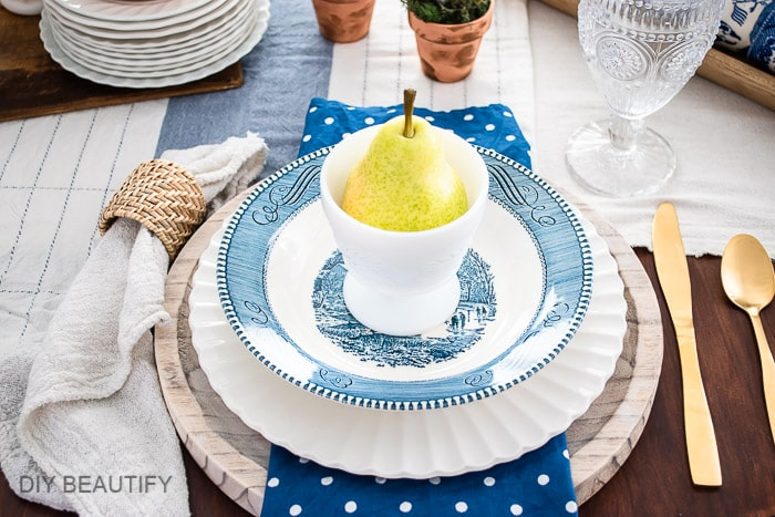 vintage dishes, gold flatware, and textured napkin holders