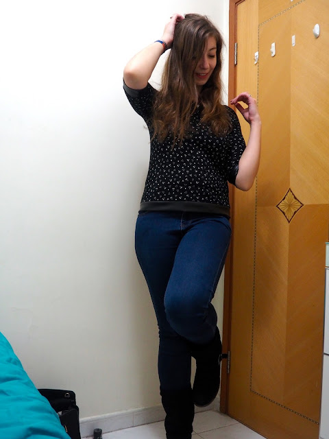 Triangular Touches - outfit of black top with white pattern and leather hems, high waist blue skinny jeans, and tall black suede boots