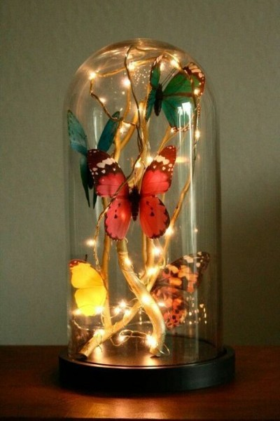Glass Cloche Filled with Butterflies, fairy lights and golden branches. Foto: Magical Daydream
