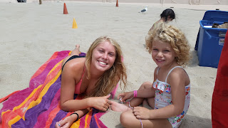 3-year-old child sitting down on the beach with her camp counselor at Aloha Beach Camp's Keiki Camp program.