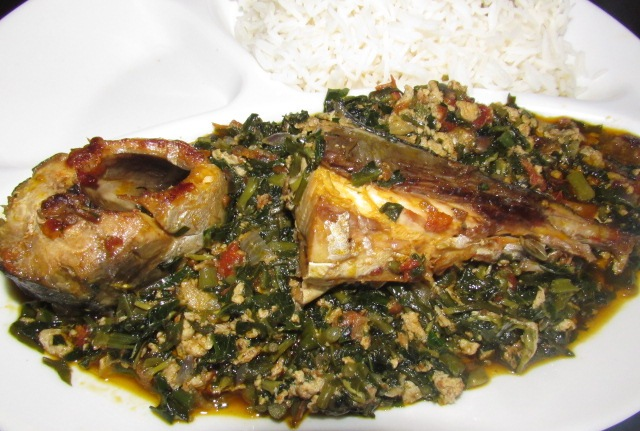 sERVING OF UGU VEGETABLE STEW WITH FISH AND BOILED RICE
