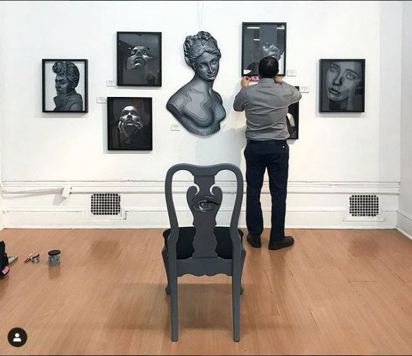 paper art exhibit of layered paper portraits in the midst of being hung on gallery wall