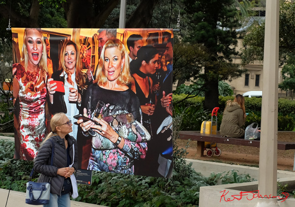 An outdoor large format print of 'Three ladies at the Billich Gallery 30th Anniversary Party' on display in Hyde Park Sydney. Street Fashion Sydney by Kent Johnson.