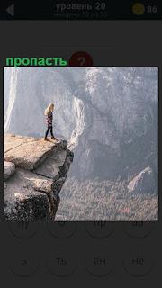 На скале стоит девушка и смотрит вниз в глубокую пропасть