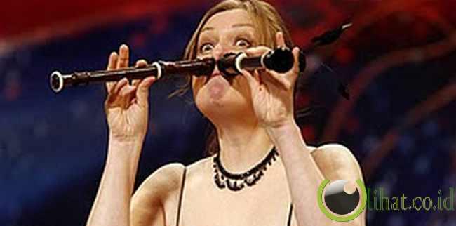 Perempuan yang memainkan dua seruling dengan hidungnya