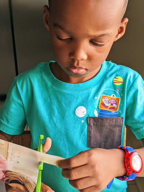 African-American boy using child-safe scissors to practice cutting