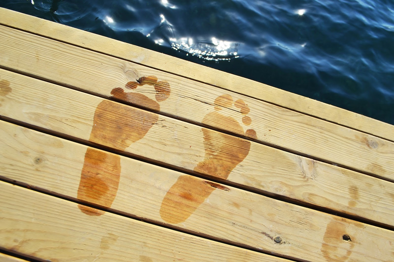 wet footprints on a wooden jetty