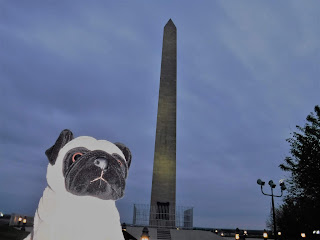 a stone obelisk appears against a blue sky, with a plush pug in the foreground
