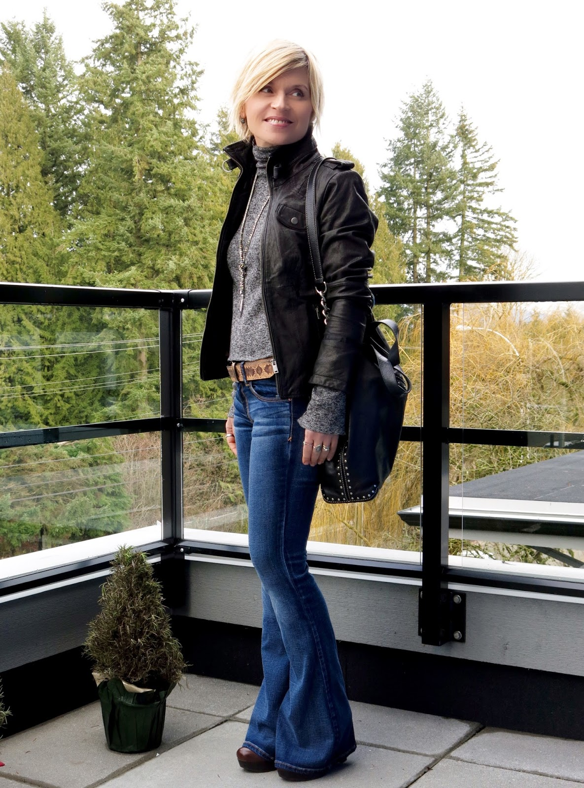 styling a motorcycle jacket with a turtleneck and and flare jeans