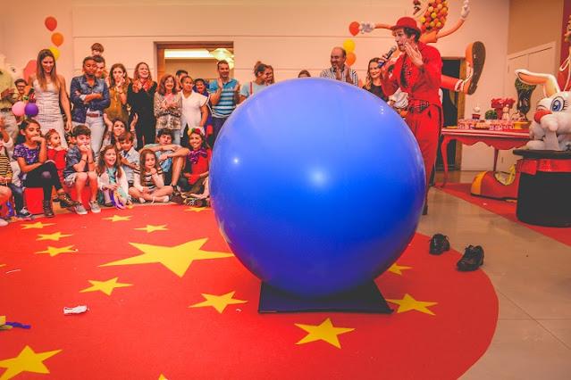 Atrações se apresentando e público ao redor assistindo atento e se divertindo em festa tema circo