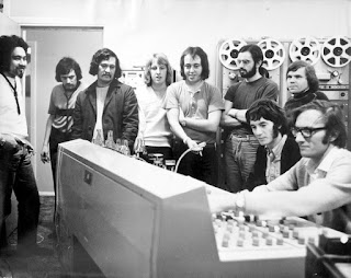 Peter Dawkins with Quincy Conserve at HMV studio in early 1971. From left: Dennis Mason, John McCormick, Rufus Rehu, Barry Brown-Sharpe, Dave Orams, Richard James Burgess, and Malcolm Hayman. Seated are Peter Dawkins and engineer Peter Hitchcock. Visible behind Rehu is the top unit of the 4-track Ampex tape recorder.