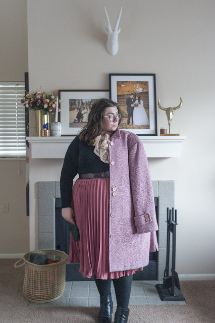 An outfit consisting of a pink marled coat, a black thrifted sweater tucked into a pink pleated tea length skirt and black chelsea boots.