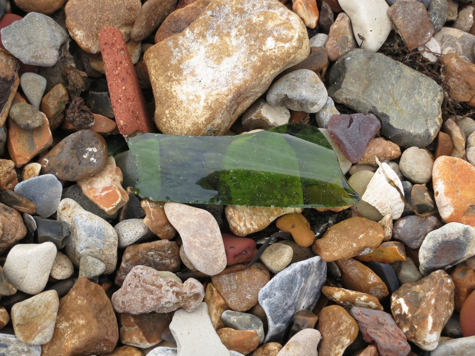 Piece of Broken glass lying on many coloured pebbles on beach