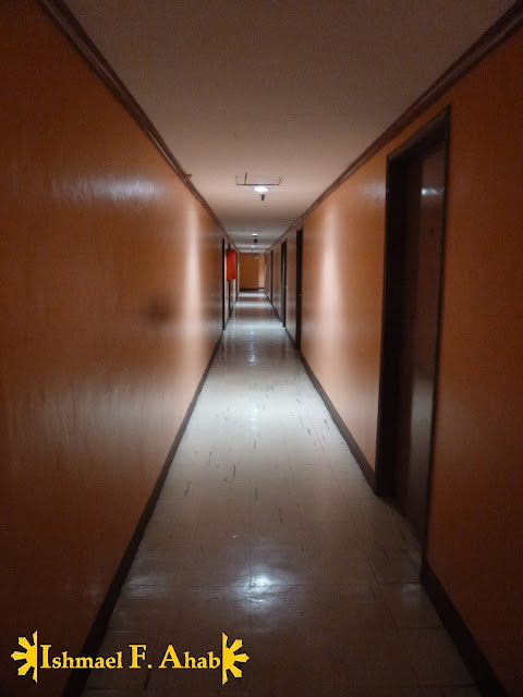 The darkly lit hallway of Pacific Tourist Inn - Cebu Hotel