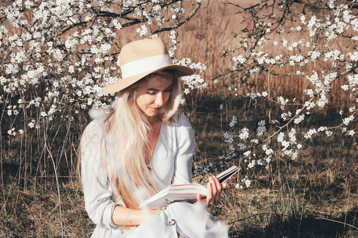 Woman wearing a white dress and a straw hat, sitting under cherry blossoms trees reading a book. Women's History Month - Celebrating our favourite women authors on Blogger's Bookshelf