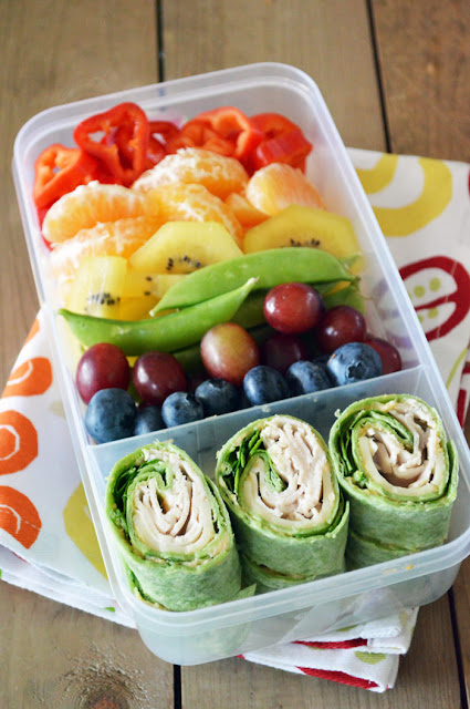 "We all know the saying, ""Eat a Rainbow!"" and with this colorful bento box lunch, your kiddos will be! This rainbow lunchbox pairs a variety of fruits and veggies with simple pinwheels filled with hummus, turkey and spinach."