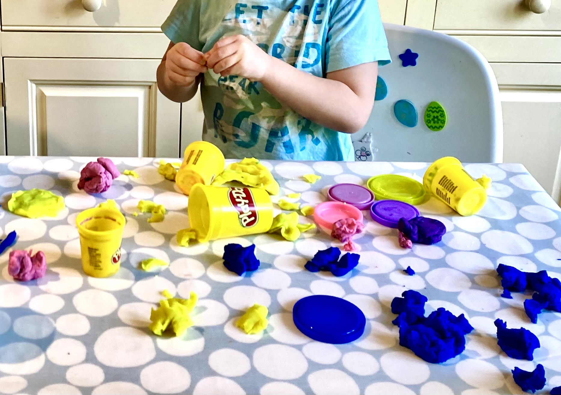 Blue, yellow and pink play-doh all over a table in separate clumps