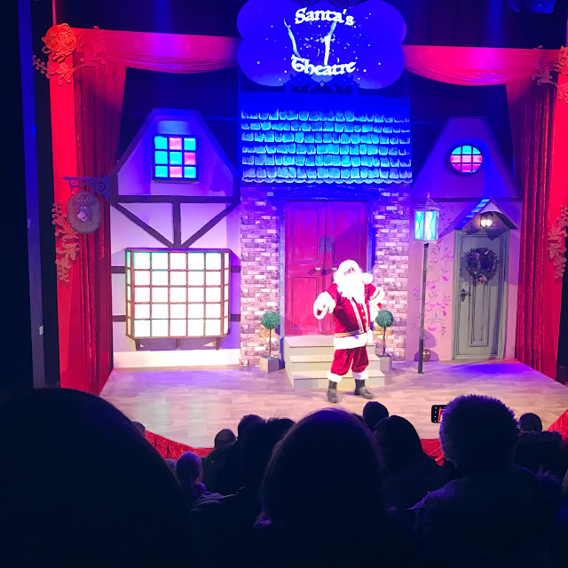 Santa on a stage in front of a shop front scenery