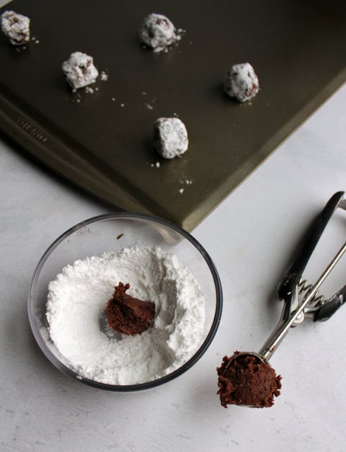 cookie scoop filled with chocolate cookie dough, ball of dough in small bowl of powdered sugar, and sugar coated balls of dough on cookie sheet