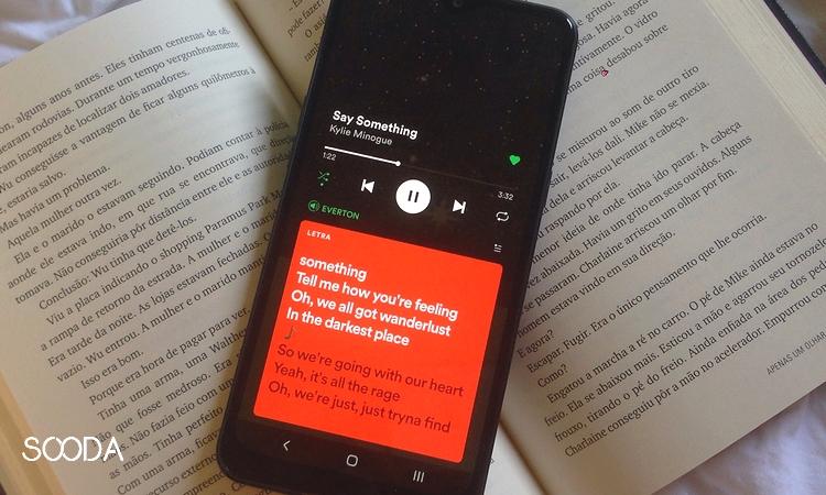 celular com algumas frases da musica say something em cima de um livro aberto