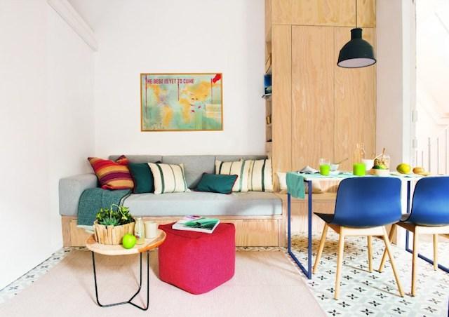 Salón con sofá coma y mesa de comedor. Mueble de madera a medida que funciona como  estantería y respaldo.