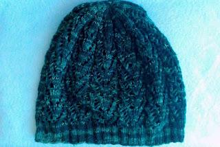 A knit lace hat.  Hat is knit in deep green tonal fingering-weight yarn.