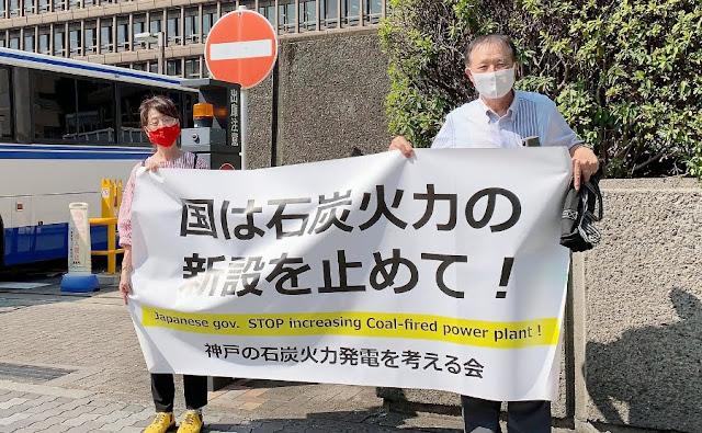 大阪高裁正門前で「国は石炭火力の新設を止めて!」と書いた横断幕を掲げる筆者の近藤秀子さんと原告団長の廣岡豊さん。