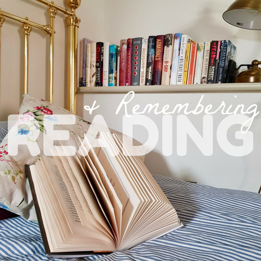 an open book rests on a pillow on a bed with a blue stripe duvet cover, with a shelf of books in the background