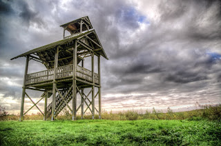 A wooden viewing tower on a grassy landscape, under a mostly cloudy sky.