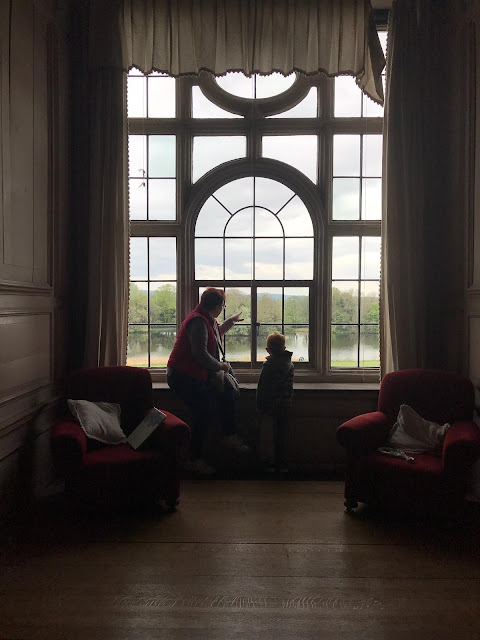 Mother and son looking out of a large stately window