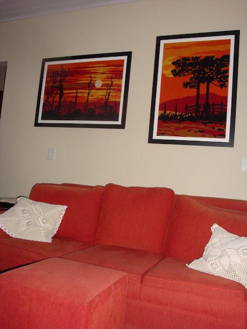 Quadros de tapeçaria e sofás vermelhos