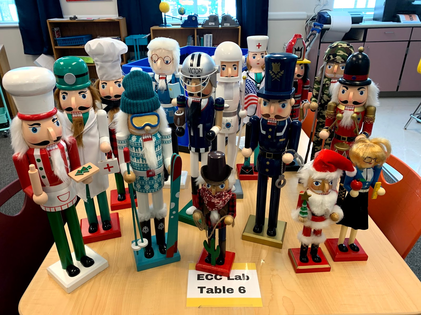 A group of a variety different types of Nutcracker dolls sit on a table.