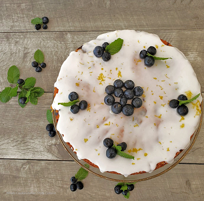 this is a blueberry doctored cake mix cake with a lemon frosting, lemon zest on top and blueberries, The cake is on a glass cake plate and there are blueberries and mint on the board
