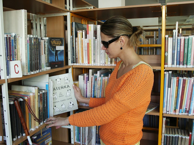 Linda prohlíží knihy v knihovně