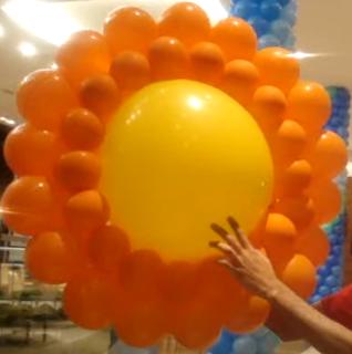 Sonne als Ballonmodellage in gelb und orange.